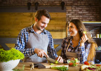 Young smiling couple cooking together