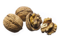 Whole walnuts and cracked walnuts on a white background