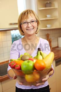 Seniorin bietet Obst an