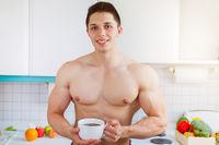 Bodybuilder junger Mann trinkt trinken Kaffee in der Küche morgens Morgen