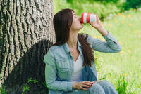 Girl with coffee in park