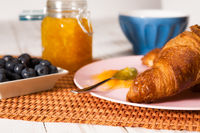 Closeup of croissant and blueberries over a tablecloth
