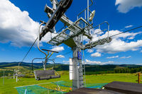 Empty chairlift in ski resort. Shot in summer with green grass and blue sky
