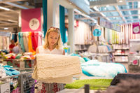 Woman choosing the right item for her apartment in a modern home furnishings store.