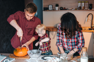 Dad, mom and little son cook a pie