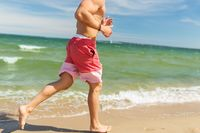 happy man running along summer beach