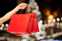 close up of hand with shopping bags at christmas