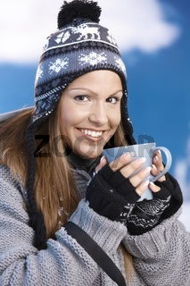 Attractive skier drinking hot drink smiling
