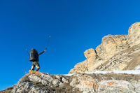 Hiker hipster with a large backpack at the foot of the epic rocks declares intention to win.