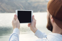 Hipster person holding in hands digital tablet with empty blank screen, man photograph on computer on background nature outdoor landscape mock up technology blur male hands tourist using gadget. Bearded hipster make a picture on nature