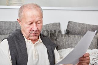 Alter Mann mit Dokument oder Rechnung