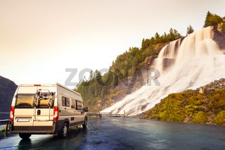 Camping van at beautiful huge waterfall. Amazing cataract at road in sunset light. Norway.