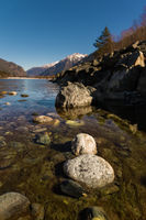 Midday Autumn landscape calm river in the Caucasus Mountains with rocks in the near term
