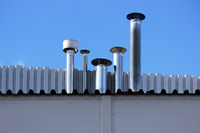 Four chimney pipe from metal on the roof of the house.