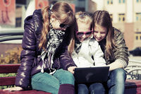 Teenage school girls using laptop on the bench
