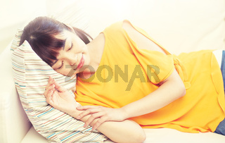 happy asian teenage girl sleeping on sofa at home