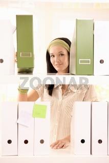 Pretty office girl arranging folders