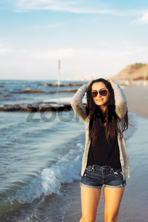 Young beautiful girl posing by the sea