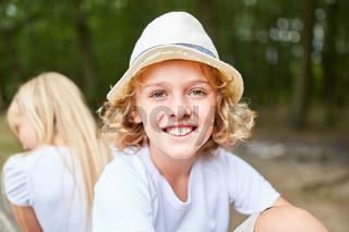 Lächelnder blonder Junge mit Strohhut