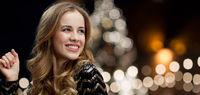 happy woman dancing over christmas tree lights