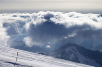 Snowy ski slope and sunlight storm clouds
