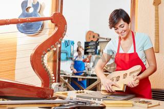 Junge Frau als Gitarrenbauer Azubi