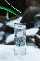 Pure mineral water is poured from a glass green bottle into a clear glass beaker until the last drop.