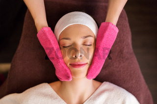 woman having face massage with terry gloves at spa
