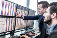 Stock traders looking at market data on computer screens.
