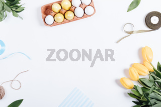 Frame of Easter eggs, yellow flowers, boxes of gifts and ribbons