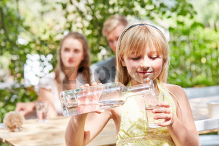 Mädchen gießt sich frisches Wasser ein