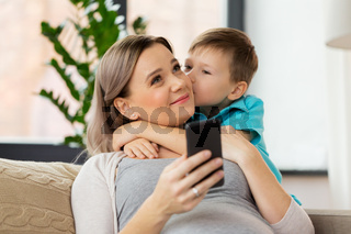 son kissing happy pregnant mother at home