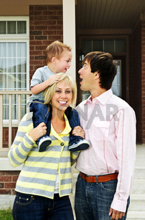 Happy family in front of home
