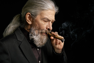 Side view of wrinkled stylish man with a cigar.
