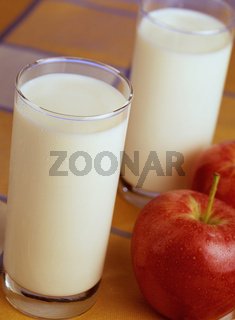 Milchglaeser und Apfel