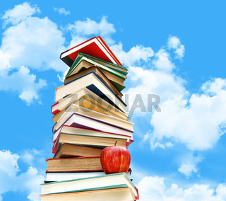 Pile of books and apple against blue sky