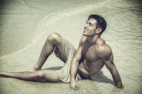 Young man laying on beach by the ocean