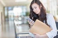 Studentin liest Nachricht auf dem Smartphone