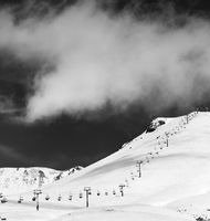 Black and white view on chair-lift and ski slope in sun day