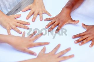 Mehrere Kinder legen Hände auf den Tisch