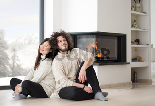 happy multiethnic couple  in front of fireplace