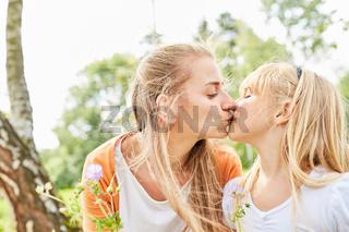 Mutter gibt ihrer Tochter liebevoll einen Kuss