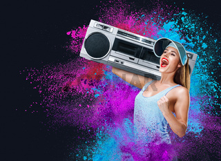 Happy young woman listening music with boombox