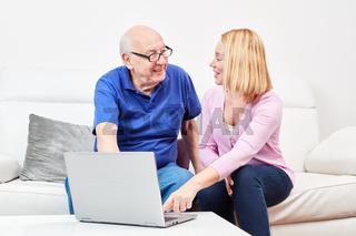 Junge Frau erklärt einem Senior einen Laptop