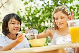 Zwei Mädchen essen Müsli und trinken Milch