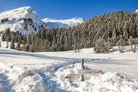 Hiking trail signpost sticks out of deep snow in mountains winter landscape on sunny day. Allgau, Bavaria, Germany.