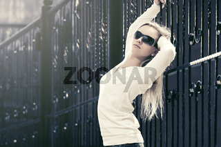 Blond fashion woman in sunglasses next to iron fence