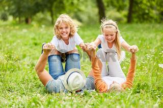 Familie und Kinder spielen auf einer Wiese