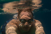 Tourist man in swimming sports glasses swimming underwater in the Aegean Sea on the coast of Sithonia Peninsula