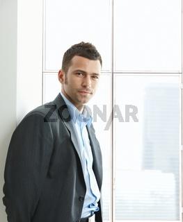 Portrait of businessman at office window